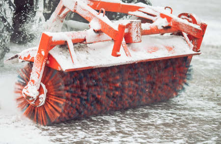 City service cleaning snow , a small tractor with a rotating brush clears a road in the city park Stockfoto