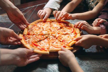 Hände, die Pizzascheiben vom Holztisch nehmen, Nahaufnahme
