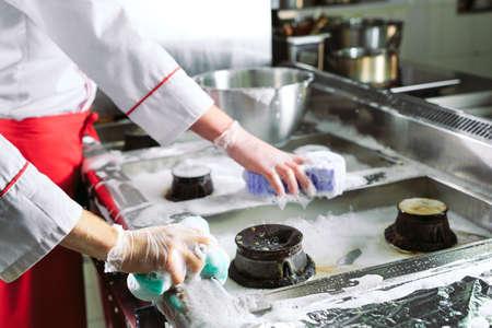 Hygienetag im Restaurant. Wiederholungen waschen Ihren Arbeitsplatz. Köche waschen Ofen, Herd und Dunstabzugshaube im Restaurant