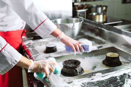 Sanitary day in the restaurant. Repeats wash your workplace. Cooks wash oven, stove and extractor in the Restaurant 版權商用圖片 - 128657110