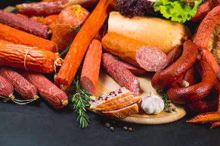 Different types of sausages and meat products on a black background