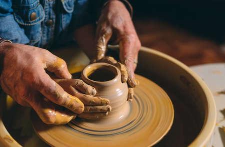 Taller de alfarería. El abuelo enseña cerámica a su nieta. Modelado de arcilla.