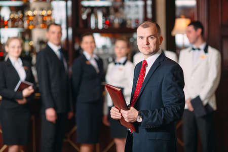 The interaction of the staff. Hotel or restaurant manager and his staff in kitchen. interacting to head chef in commercial kitchen.