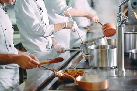 Chef cocinando verduras en sartén wok. Kelvin superficial.