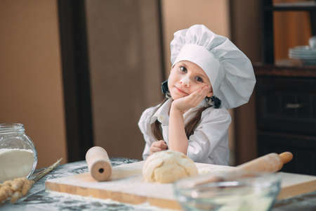 girl kid are preparing the dough in the kitchen.