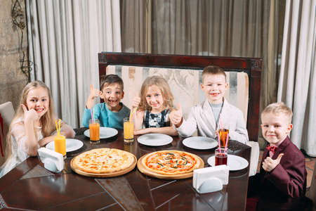 Groupe of Children eat pizza in the restaurant. Imagens
