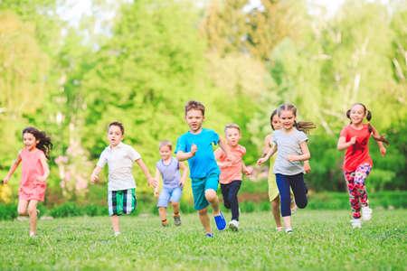 Molti bambini, ragazzi e ragazze diversi che corrono nel parco durante la soleggiata giornata estiva in abiti casual.