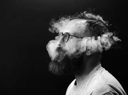 Concept. Smoke enveloped the head man. Portrait of a Bearded, stylish man with smoke. Secondhand smoke 版權商用圖片