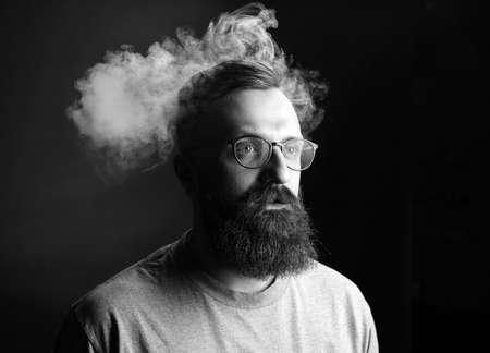 Concept. Smoke enveloped the head man. Portrait of a Bearded, stylish man with smoke. Secondhand smoke Фото со стока