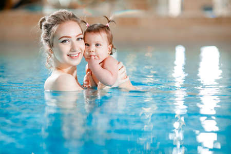 Mom and baby swim in the pool.