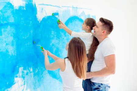 Madre, padre e hija pintando la pared de su nuevo hogar.