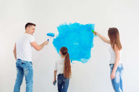 Mother, father and little daughter painting the wall in their new home.