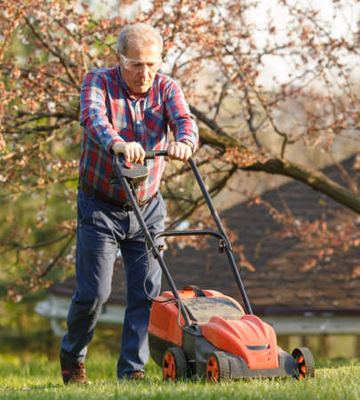 Man with electric lawnmower, lawn mowing. Gardener trimming a garden. Sunny day, suburb, village.