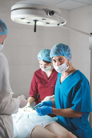 Portrait of surgeons at work, operating in uniform, looking at camera. 写真素材