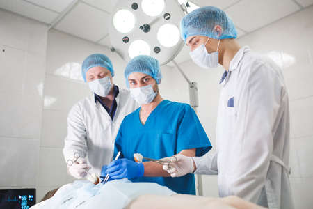 Group of surgeons at work operating in surgical theatre. Resuscitation medicine team wearing protective masks holding steel medical tools