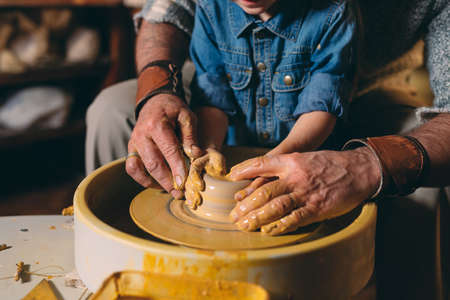 Pottery workshop. Grandpa teaches granddaughter pottery. Clay modeling 写真素材 - 128594914