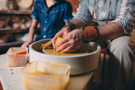 Pottery workshop. Grandpa teaches granddaughter pottery. Clay modeling 写真素材 - 128594928