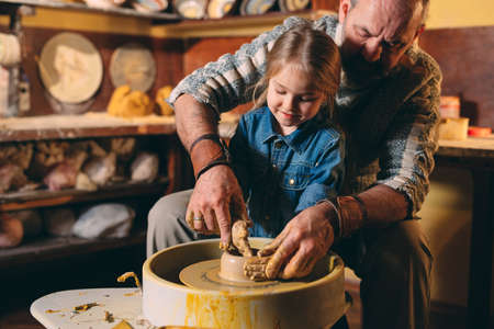 Pottery workshop. Grandpa teaches granddaughter pottery. Clay modeling 写真素材 - 128594849
