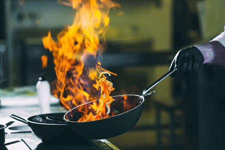Lo chef sta mescolando le verdure durante il lavoro in cucina. Archivio Fotografico