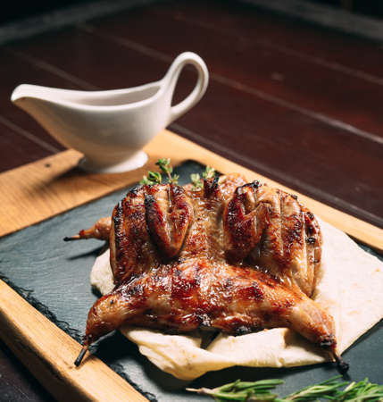 Grilled quails on wooden plate on the table
