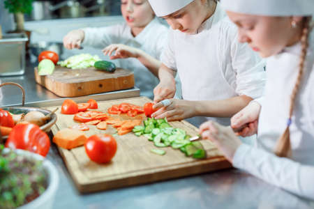 Children in chefs hat grind vegetables on the kitchen.