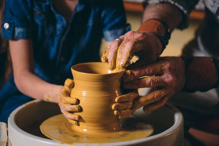 Pottery workshop. Grandpa teaches granddaughter pottery. Clay modeling 写真素材 - 128594314