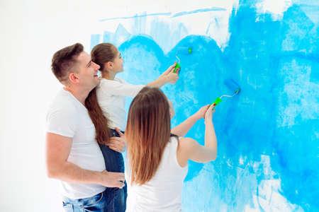 Madre, padre e figlia piccola dipingono il muro nella loro nuova casa.