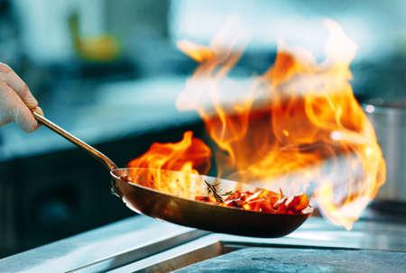 Cuisine moderne. Les cuisiniers préparent les repas sur la cuisinière dans la cuisine du restaurant ou de l'hôtel. Le feu dans la cuisine.