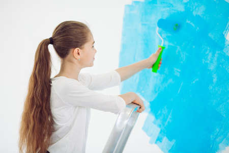 Repair in the apartment. Happy child girl paints the wall with blue paint,