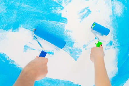 blue color painting wall with roller in hand.