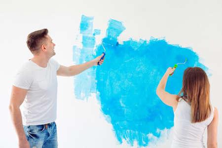Heureux couple peignant des murs dans leur nouvelle maison prête à vivre ensemble.