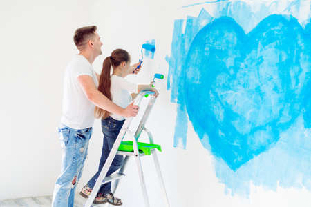 Father and his little daughter painting a wall in new home.