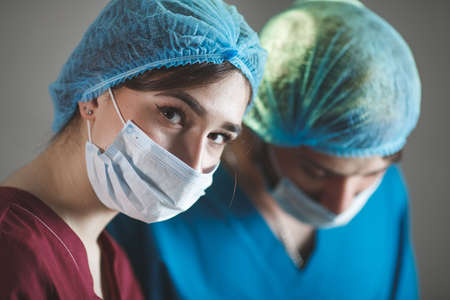 Portrait of surgeons at work, operating in uniform, looking at camera. Фото со стока