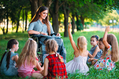 Disabled teacher conducts a lesson with children in nature. Interaction of a teacher in a wheelchair with students.