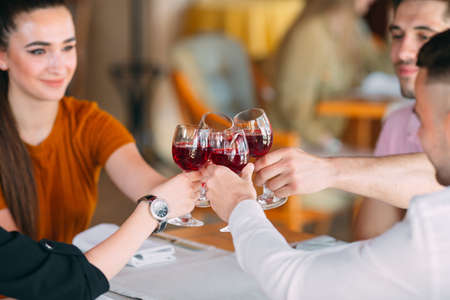 Friends drink wine on the terrace of the restaurant.