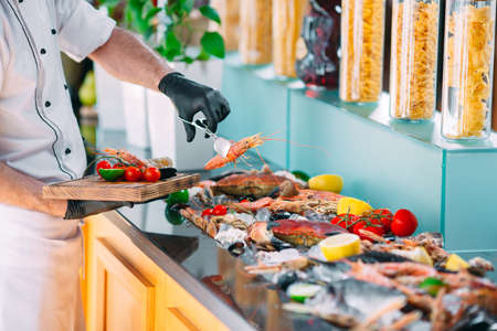 The Chef puts the seafood on a tray in the restaurant.