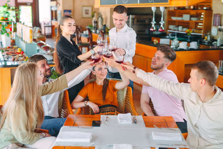 Friends drink wine on the terrace of the restaurant. Imagens