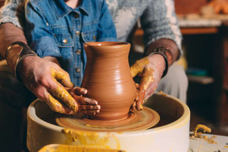 Pottery workshop. Grandpa teaches granddaughter pottery. Clay modeling 写真素材 - 128594098
