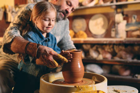 Pottery workshop. Grandpa teaches granddaughter pottery. Clay modeling 写真素材 - 128594104