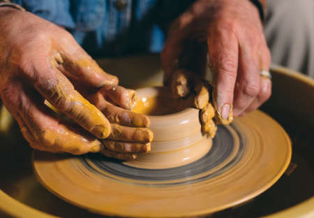 Pottery workshop. Grandpa teaches granddaughter pottery. Clay modeling 写真素材 - 128594174