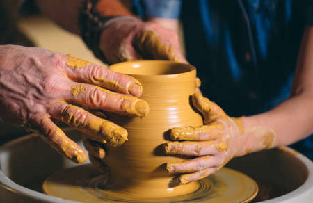 Pottery workshop. Grandpa teaches granddaughter pottery. Clay modeling 写真素材 - 128594178