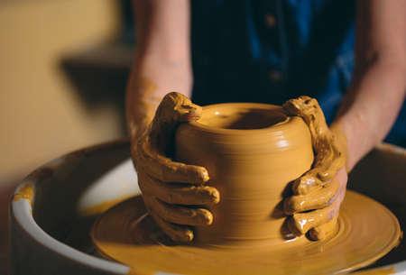 Töpferwerkstatt. Ein kleines Mädchen macht eine Vase aus Ton. Modellieren aus Ton