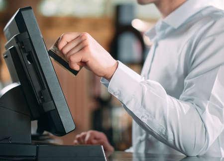 piccola impresa, persone e concetto di servizio - uomo felice o cameriere in grembiule al bancone con cassa che lavora al bar o alla caffetteria. Archivio Fotografico