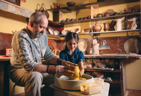 Pottery workshop. Grandpa teaches granddaughter pottery. Clay modeling