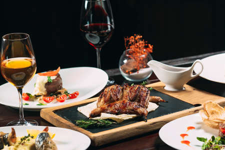 Grilled partridge, sea bass, Tartarus. Different dishes on the table in the restaurant