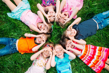 A group of children lying on the green grass in the Park. The interaction of the children. Imagens