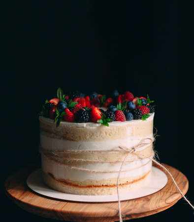 Fruit cake. Cake decorated with berries on a wooden stand on a black background.