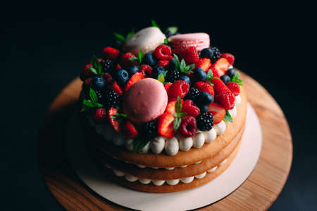 Fruit cake. Cake decorated with berries on a wooden stand on a black background Imagens - 128596497