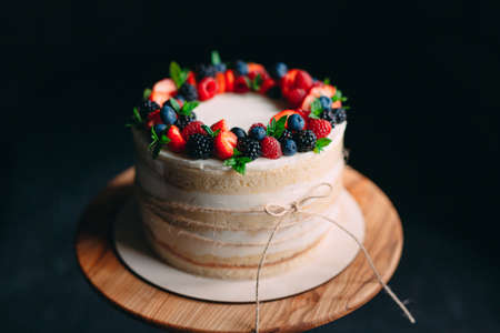 Fruit cake. Cake decorated with berries on a wooden stand on a black background Stock Photo