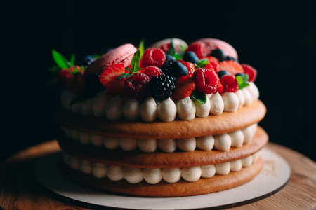 Fruit cake. Cake decorated with berries on a wooden stand on a black background Imagens - 128596438